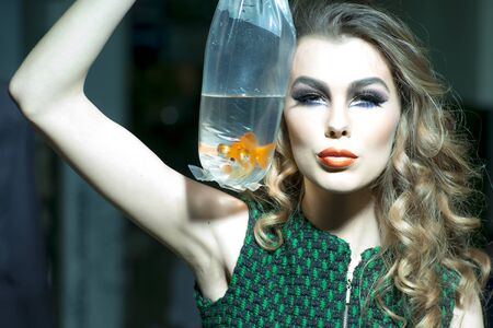 skintone: Winning young girl with bright makeup and blonde curly hair holding cellophane package aquarium with goldfish, horizontal photo Stock Photo