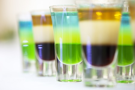 shooter drink: Colorful shot alcoholic cocktails green blue white brown and gold colours standing in a row on table top in glasses closeup of drinks background, horizontal picture Stock Photo