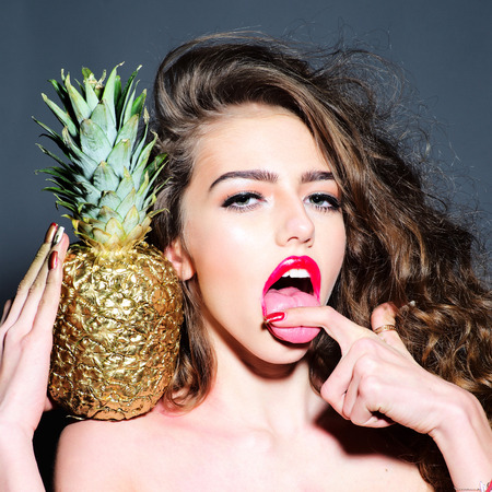 Portrait of sexy young girl with curly hair and bright pink lips  holding golden pineapple on shoulder looking forward with open mouth touching her tongue with finger standing on dark background, square picture
