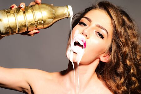 Tempting attractive young woman with curly hair holding gold bottle pours white yogurt on her face with open mouth looking forward standing on grey background, horizontal picture