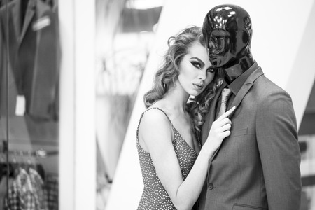 male mannequin: Enigmatic young woman with bright makeup and curly hair standing with male mannequin in formal clothes on shopping background black and white, horizontal picture Stock Photo