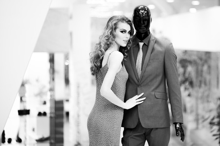 male mannequin: Enigmatic young girl with bright makeup and curly hair standing with male mannequin in formal clothes on shopping background black and white, horizontal picture Stock Photo