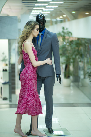 male mannequin: Tempting young girl with bright makeup and curly hair standing with male mannequin in formal clothes on shopping background, vertical picture