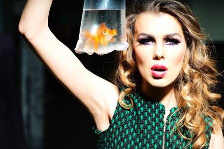 skintone: Dramatic young girl with bright makeup and blonde curly hair holding cellophane package aquarium with goldfish, horizontal photo