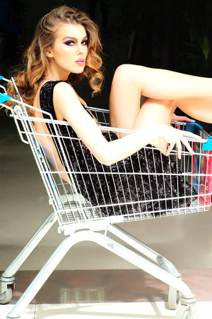 misterious: One misterious fashion woman in black dress sitting in shopping trolley indoor on shop background vertical picture