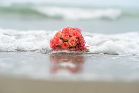 soggy: Bouquet of scarlet roses lying on sandy beach with surf closeup on water background horizontal picture