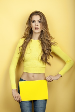 one sheet: Thin attractive young woman with long curly hair in blouse and blue jeans holding one bright yellow sheet of paper standing on yellow background, vertical picture