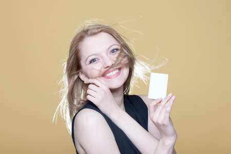 Happy young blonde girl with blank business card on beige background Stock Photo