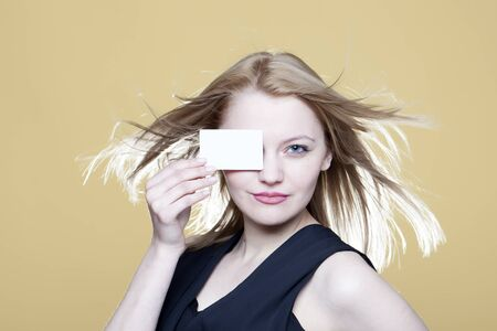 notecard: Beautiful young girl with blank business card on beige background Stock Photo