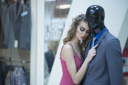 misterious: Misterious young girl with bright makeup and curly hair standing with male mannequin in formal clothes on shopping background, horizontal picture