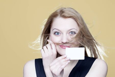 notecard: Beautiful young blonde girl holds blank business card on beige background