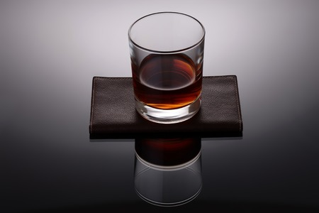 One glass cup with strong amber alcoholic drink reflecting and standing on brown leather napkin on grey and white background, horizontal picture