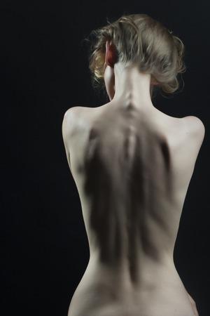 donna completamente nuda: Bella sottile svestita perfetta forma del corpo femminile seduta con vista posteriore su sfondo nero, immagine verticale