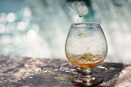 Amber alcoholic drink poured in glass stnading on stone rim of fountain on water splashes background copyspace, horizontal picture