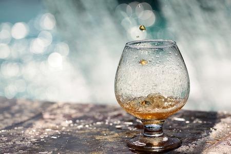 tomando alcohol: Bebida alcohólica ámbar vierte en stnading vidrio en el borde de piedra de la fuente en el agua salpica fondo copyspace, horizontal de la imagen