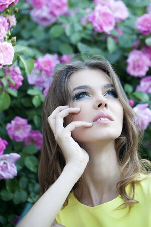 Portrait of attractive thoughtful young blonde woman with bright makeup and curly hair with lush bush of pink rose, vertical picture photo