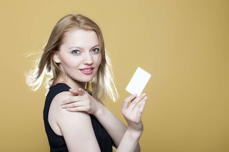 notecard: Smiling young blonde girl with blank business card on beige background Stock Photo