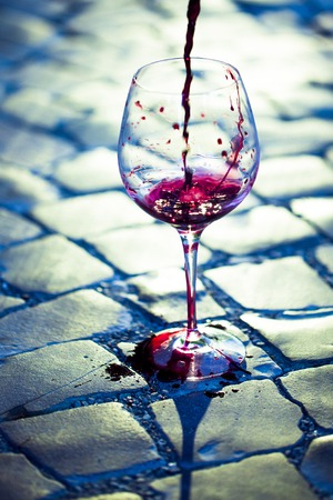 taster: Red wine poured in glass standing on block stone road in daylight on outdoor background, vertical picture