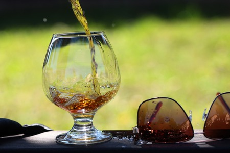 bocal: Amber alcoholic beverage poured in bocal stnading on table near sunglasses on natural background, horizontal picture Stock Photo