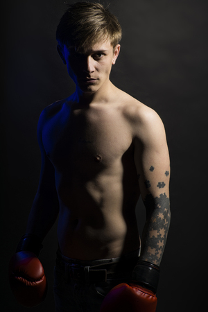 black shadow: Young serious muscular man in red boxing gloves standing in shadow looking forward on black background copy space, vertical photo