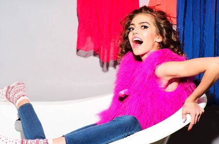 pink fur: Smiling emotional young woman with curly hair in pink fur vest and blue jeans sitting in white bathtub amid colorful clothes pink orange red blue colors on grey wall background, horizontal picture