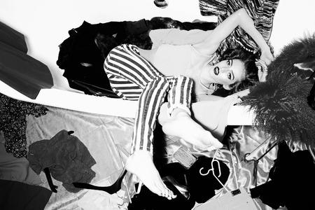 rosa negra: Llamativo mujer joven brillante con el pelo rizado que miente en la bañera en medio de ropa en la pared de fondo negro y el blanco, cuadro horizontal