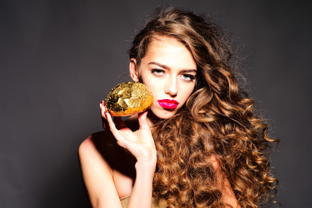 nude pretty girl: Charming young girl with curly hair and bright pink lips holding golden bread roll near face looking forward standing on dark grey background, horizontal picture Stock Photo