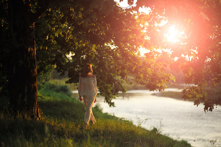 Beautiful young woman in white clothes standing on river bank in calm on natural sunset background, horizontal picture