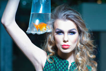 skintone: Striking young girl with bright makeup and blonde curly hair holding cellophane package aquarium with goldfish, horizontal photo