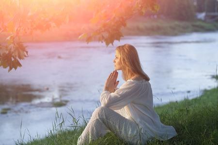 silencio: Misteriosa mujer joven en la ropa blanca que se sienta en la orilla del río en calma en el fondo la puesta del sol natural, horizontal de la imagen