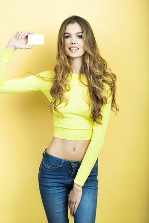 one sheet: Slender alluring young girl with long curly hair in yellow blouse and blue jeans holding one small white sheet of paper standing on yellow background, vertical picture Stock Photo