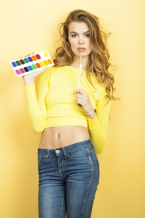 Beautiful sexy young woman in blouse and blue jeans holding colorful palette and paint brush standing on yellow wall background, vertical picture