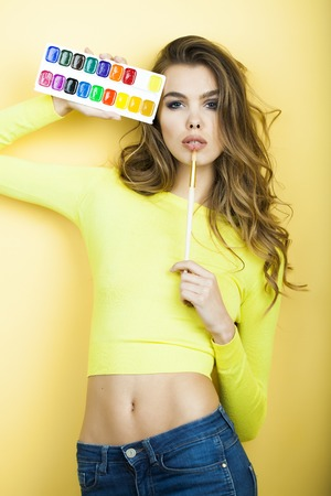 vetical: Pretty sensual young girl in blouse and blue jeans holding colorful paint palette standing on yellow wall background, vertical picture Stock Photo