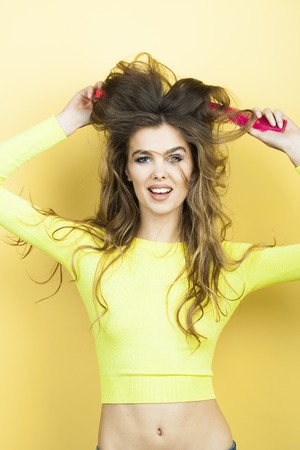 hair model: Pretty smiling playful young woman with long curly hair in yellow blouse and blue jeans holding two pink hair brushes standing on yellow background, vertical picture Stock Photo