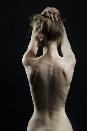 anatomy naked woman: Beautiful thin naked female body perfect shape sitting with back view on black background, vertical picture