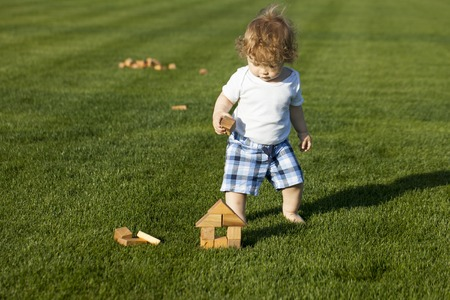 full height: Cute curly baby boy full height in the plaid shorts building a wooden house on green meadow sunny day outdoor, horizontal photo