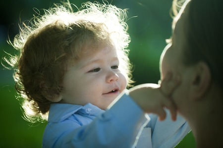 explores: Portrait of a little curly baby boy explores and touching moms face carefully with love outdoor closeup, horizontal photo