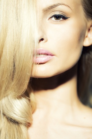 Portrait of stylish attractive lady with silk blonde hair and tender makeup closeup, vertical picture