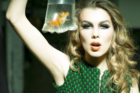 skintone: Tempting young girl with bright makeup and blonde curly hair holding cellophane package aquarium with goldfish, horizontal photo Stock Photo