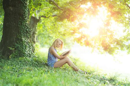 Mooie verleidelijke blonde vrouw zitten buiten met boek in de zomer op groene natuurlijke achtergrond, horizontaal beeld
