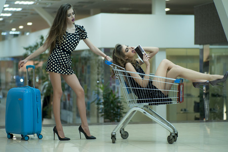 shopping baskets: Two cute attractive girls in dresses with shopping trolley and blue bag indoor on shop background, horizontal picture