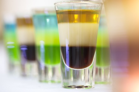 shooter drink: Multicolored shot alcoholic cocktails green blue white brown and gold colours standing in a line on table top in glasses closeup of drinks background, horizontal picture