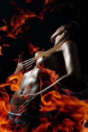 Erotic sexuelle jeune femme dévêtue avec un beau corps droit debout au feu orange et rouge sur fond noir, verticale de l'image Banque d'images - 41594368