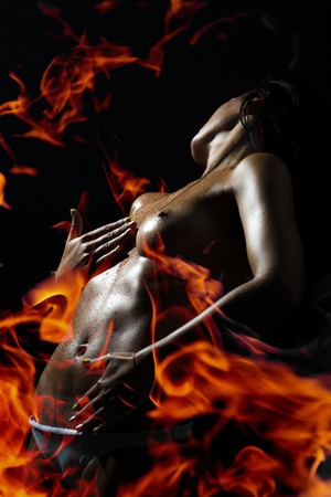 Erotic sexual undressed young lady with straight beautiful body standing in orange and red fire on black background, vertical picture Stockfoto