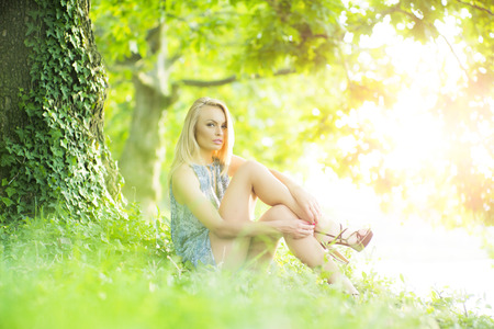 Attractive sexy slender woman outdoor in summer clothes in park on green natural background, horizontal picture Stock Photo