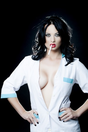 sex pose: Passionate pretty young brunette doctor in white uniform smoking standing on black background, vertical picture Stock Photo