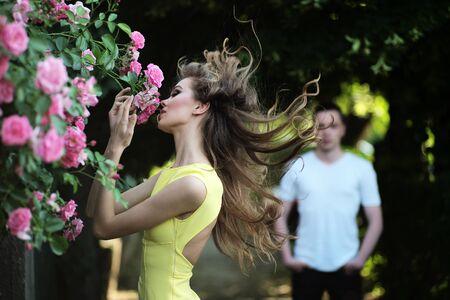 mujer con rosas: La mujer rubia joven sexual con maquillaje brillante y el pelo rizado en vestido amarillo con olor exuberante mata de rosa rosa y hombre en el fondo, cuadro horizontal