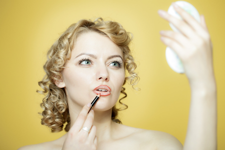Blond woman in a white dress rouges with lipstick