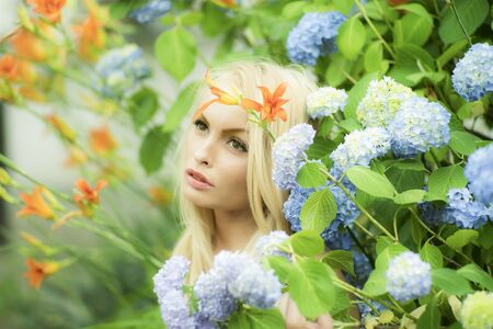 Pensive sensible pretty woman among lush bush of hydrangea and orange flowers looking away on bright natural background, horizontal picture