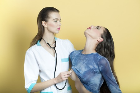 Beautiful sexy nurse in white medical uniform listening chest of sensual patient woman in blue with stethoscope standing on yellow background, horizontal picture 免版税图像